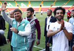 In this photo taken on Sunday, June 10, 2018, Egyptian national soccer team player and Liverpool's star striker Mohammed Salah, right, and Chechen regional leader Ramzan Kadyrov, greets soccer fans as they arrive to attend the Egypt national soccer team training session in Grozny, Russia. Egyptian national soccer team will compete in the 2018 World Cup in Russia. The 21st World Cup begins on Thursday, June 14, 2018, when host Russia takes on Saudi Arabia. (AP Photo)