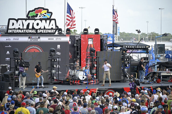 Entertainer Chris Lane, second from right, performs with a fan before a NASCAR Cup Series auto race at Daytona International Speedway, Saturday, Aug. 28, 2021, in Daytona Beach, Fla. (AP Photo/Phelan M. Ebenhack)