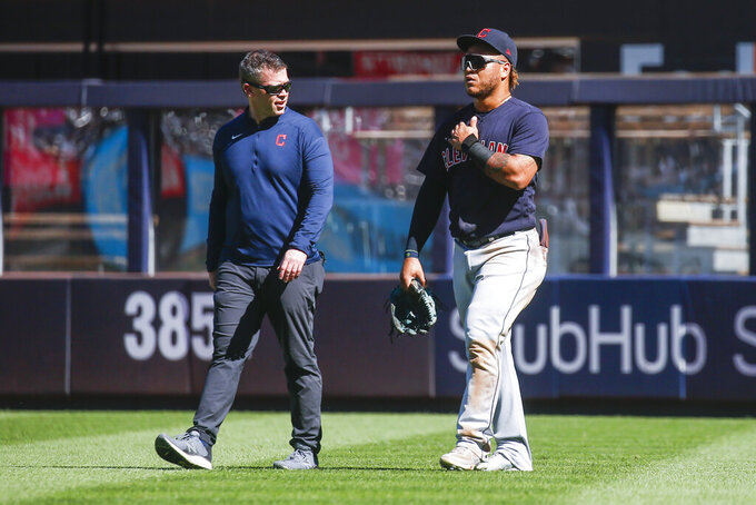 Cleveland Indians' Harold Ramirez, right, walks off the field after crashing into the wall while attempting to catch a home run by New York Yankees' Gio Urshela in the third inning of a baseball game Sunday, Sept. 19, 2021, in New York. (AP Photo/Eduardo Munoz Alvarez)
