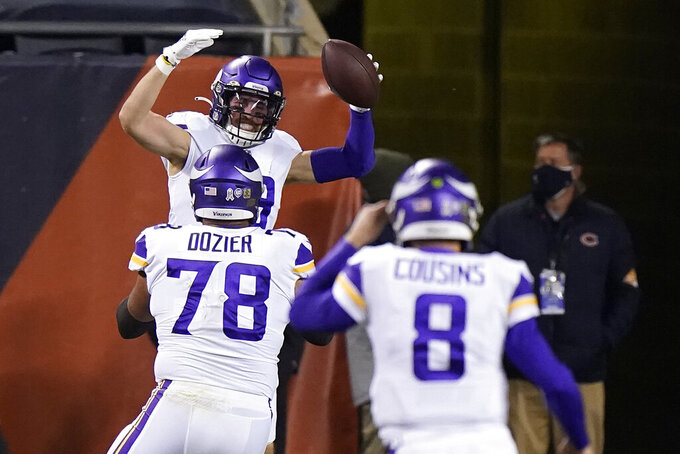 Minnesota Vikings wide receiver Adam Thielen celebrates with teammates guard Dakota Dozier (78) and quarterback Kirk Cousins (8) after catching a touchdown pass during the first half of an NFL football game against the Chicago Bears Monday, Nov. 16, 2020, in Chicago. (AP Photo/Nam Y. Huh)