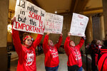 Indiana teachers wearing red have carry signs as they hold rally at the Statehouse in Indianapolis, Tuesday, Nov. 19, 2019, calling for further increasing teacher pay in the biggest such protest in the state amid a wave of educator activism across the country. Teacher unions says about half of Indiana's nearly 300 school districts are closed while their teachers attend Tuesday's rally while legislators gather for 2020 session organization meetings.(AP Photo/Michael Conroy)
