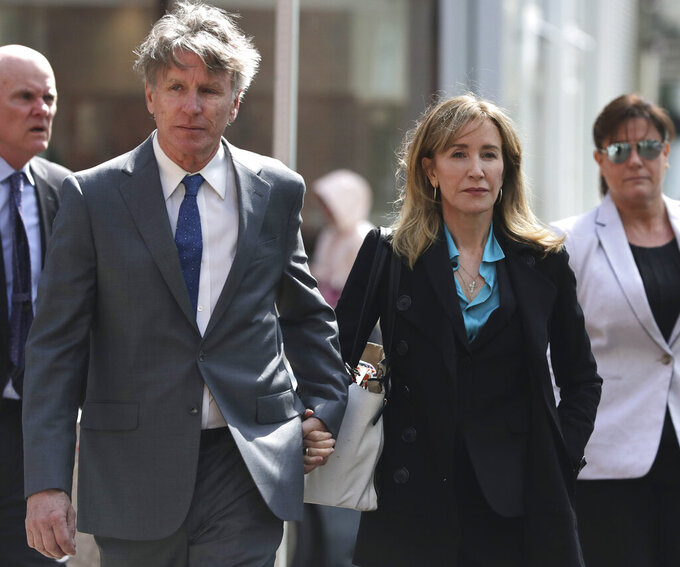 ADDS IDENTIFICATION OF MAN AS MOORE HUFFMAN JR. -Actress Felicity Huffman arrives holding hands with her brother Moore Huffman Jr., left, at federal court in Boston on Wednesday, April 3, 2019, to face charges in a nationwide college admissions bribery scandal. (AP Photo/Charles Krupa)