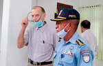 FILE - In this Feb. 22, 2021, file photo, a police officer escorts Richard Daschbach, center, a former missionary from Pennsylvania, U.S. upon his arrival for a trial at a courthouse in Oecusse, East Timor. The defrocked American priest went on trial Tuesday, Feb. 23,  to face charges he sexually abused young girls at his shelter for orphans and children from impoverished families, marking the first clergy sex case to emerge in East Timor — the most Catholic place in the world outside the Vatican.   (AP Photo/File)