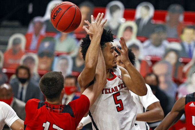 Incarnate Word's Dakota Reber (12) and Texas Tech's Micah Peavy (5) fight for the rebound during the first half of an NCAA college basketball game Tuesday, Dec. 29, 2020, in Lubbock, Texas. (AP Photo/Brad Tollefson)