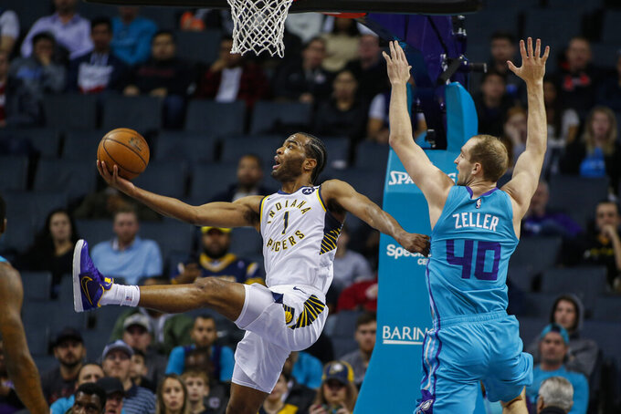 Indiana Pacers forward T.J. Warren, left, shoots a scoop shot as he drives past Charlotte Hornets forward Cody Zeller in the first half of an NBA basketball game in Charlotte, N.C., Monday, Jan. 6, 2020. (AP Photo/Nell Redmond)