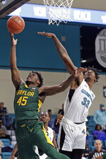 Baylor guard Davion Mitchell (45) drives to the basket against Coastal Carolina forward Tommy Burton (33) during the second half of an NCAA college basketball game at the Myrtle Beach Invitational in Conway, S.C., Friday, Nov. 22, 2019. (AP Photo/Gerry Broome)