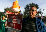 Dennis Becker, 54, from Fort Lauderdale, gathers near the BB&T Center with a giant inflatable baby of President Donald Trump before a