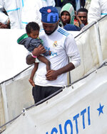 A migrant man holds a baby as they disembark from Italian Coast Guard vessell