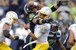 Los Angeles Chargers quarterback Chase Daniel, front right, is hit by Seattle Seahawks linebacker Cody Barton, causing a fumble that was recovered by the Seahawks for a touchdown during the first half of an NFL football preseason game Saturday, Aug. 28, 2021, in Seattle. (AP Photo/John Froschauer)
