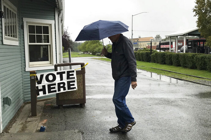 FILE - In this Aug. 21, 2018 file photo, a voter enters the Palmer Community Center to cast their ballot in Alaska's primary election, on a rainy in Palmer, Alaska. The Alaska Republican Party has canceled holding a presidential primary in 2020. In a statement Saturday, Sept. 21, 2019, the party's State Central Committee passed a rule saying a primary