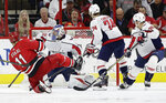 Carolina Hurricanes' Jordan Staal (11) scores against Washington Capitals goalie Philipp Grubauer (31), of Germany, during the first period of an NHL hockey game in Raleigh, N.C., Friday, Jan. 12, 2018. Capitals' John Carlson (74) and Alex Chiasson (39) look on. (AP Photo/Gerry Broome)