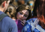 Parents greet and hug their children following a shooting at Dixon High School Wednesday, May 16, 2018, in Dixon, Ill. A 19-year-old who showed up at his former high school in northern Illinois and opened fire on a police officer working there, was shot by the officer and taken into custody. The officer, who was not injured, was hailed a hero for his quick response protecting students and staff who had gathered at Dixon High School for a graduation rehearsal. (Alex T. Paschal/Sauk Valley Media via AP)