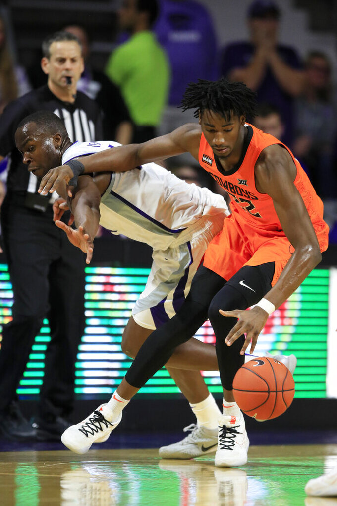 Oklahoma State forward Kalib Boone (22) spins away from Kansas State forward Makol Mawien, left, during the second half of an NCAA college basketball game in Manhattan, Kan., Tuesday, Feb. 11, 2020. Oklahoma State defeated Kansas State 64-59. (AP Photo/Orlin Wagner)