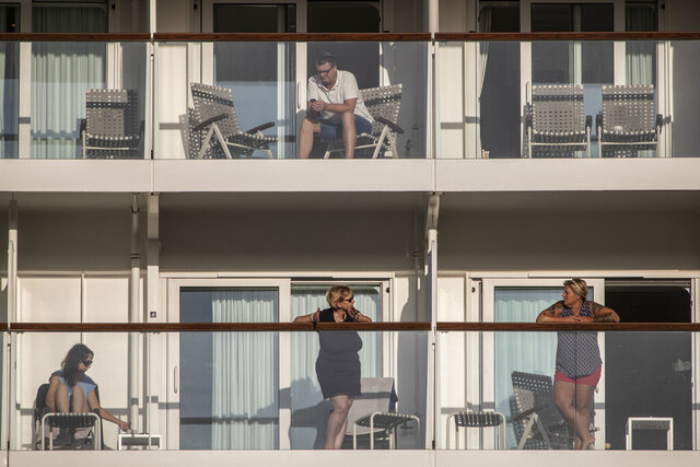 Passengers of the Mein Schiff 6 cruise ship stand outside their cabins as the ship is docked at Piraeus port, near Athens on Tuesday, Sept. 29, 2020. Greek authorities say 12 crew members on a Maltese-flagged cruise ship carrying more than 1,500 people on a Greek islands tour have tested positive for coronavirus and have been isolated on board.(AP Photo/Petros Giannakouris)