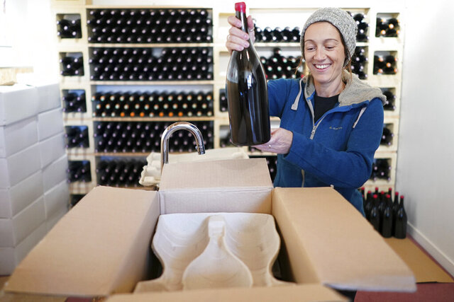In this Wednesday, Nov. 13, 2019 photo, winemaker Claire Chasselay puts bottles of wine in boxes in her cellar in Chatillon d'Azergues, in the Beaujolais region, eastern France. Celebration is the mot du jour in France's Beaujolais region on the third Thursday of November, when winemakers and sellers uncork the season's Beaujolais Nouveau with feasting and fanfare. (AP Photo/Laurent Cipriani)