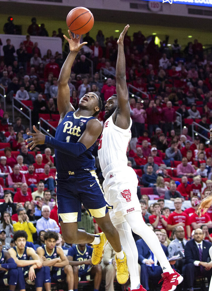 Pittsburgh's Xavier Johnson (1) attempts a shot as North Carolina State's Eric Lockett (5) defends during the second half of an NCAA college basketball game in Raleigh, N.C., Saturday, Jan. 12, 2019. (AP Photo/Ben McKeown)