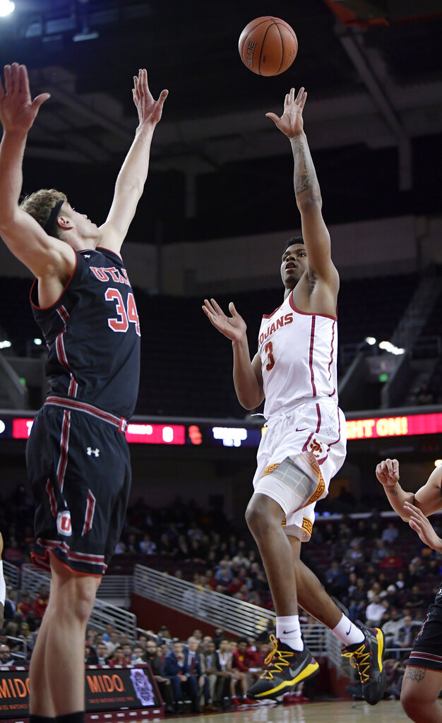 Southern California guard Elijah Weaver, right, shoots as Utah center Jayce Johnson defends during the first half of an NCAA college basketball game Wednesday, Feb. 6, 2019, in Los Angeles. (AP Photo/Mark J. Terrill)