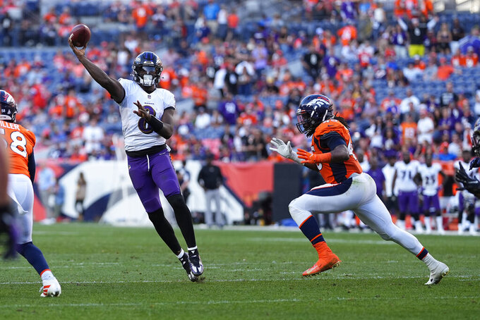 Baltimore Ravens quarterback Lamar Jackson (8) throws as Denver Broncos linebacker A.J. Johnson pursues during the second half of an NFL football game, Sunday, Oct. 3, 2021, in Denver. (AP Photo/Jack Dempsey)