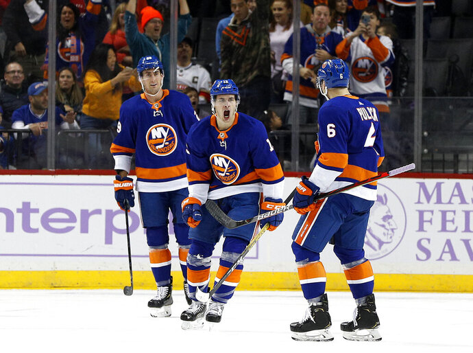 New York Islanders center Mathew Barzal (13) celebrates his goal in the first period of an NHL hockey game against the Florida Panthers with teammate Brock Nelson (29) and Ryan Pulock (6), Saturday, Nov. 9, 2019, in New York (AP Photo/Jim McIsaac)