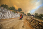 People drive away from an advancing fire in Cokertme village, in Bodrum, Mugla, Turkey, Monday, Aug. 2, 2021. For the sixth straight day, Turkish firefighters were battling Monday to control the blazes tearing through forests near Turkey's beach destinations. Fed by strong winds and scorching temperatures, the fires that began Wednesday have left eight people dead and forced residents and tourists to flee vacation resorts in a flotilla of small boats.(AP Photo/Emre Tazegul)
