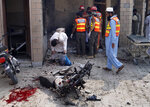 Pakistani security officials and rescue workers gather at the site of a bombing on an entrance of a hospital in Dera Ismail Khan, Pakistan, Sunday, July 21, 2019. Police in Pakistan say gunmen opened fire on a police post and then bombed the entrance to a hospital as the wounded were being brought in.(AP Photo/Ishtiaq Mahsud)