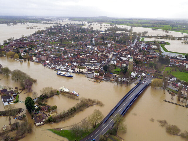 Flood water surrounds the town of Upton-upon-Severn, England, with the normal course of the river Severn running horizontally under the road bridge, in the aftermath of Storm Dennis, in this photo taken with a drone Thursday Feb. 20, 2020. The regions of north and west England and Wales already battling with the aftermath of several days of rain have been told to expect further deluges, by the Environment Agency, with severe flood warnings in some areas including the river Severn. (Steve Parsons/PA via AP)