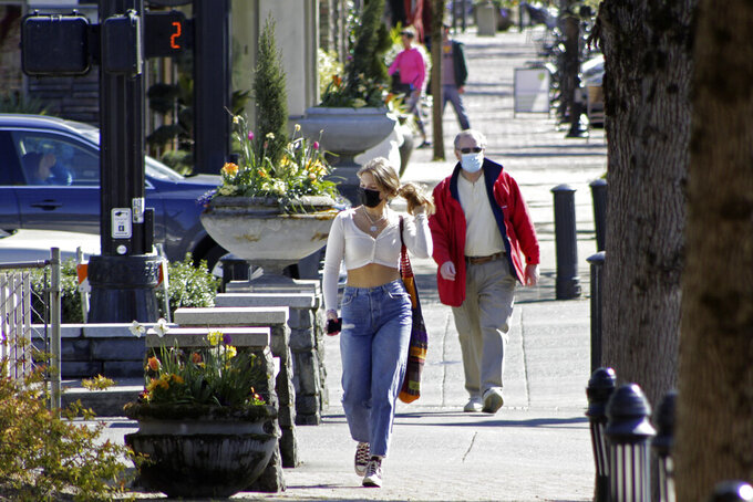 FILE - In this April 11, 2021, file photo, residents wearing masks walk in downtown Lake Oswego, Ore. Oregon Gov. Kate Brown said Tuesday, April 27, 2021 rising COVID-19 hospitalizations threaten to overwhelm doctors and she is moving 15 counties into extreme risk category, which imposes restrictions including banning indoor restaurant dining. (AP Photo/Gillian Flaccus, File)