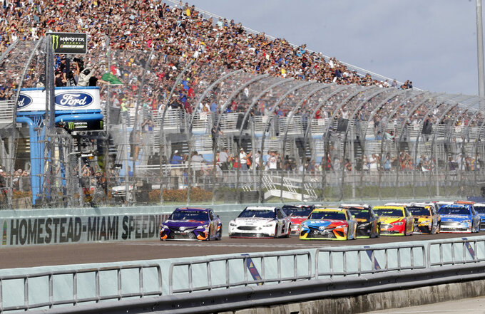 Denny Hamlin, left, leads the pack at the start of the NASCAR Cup Series championship auto race at Homestead-Miami Speedway, Sunday, Nov. 18, 2018, in Homestead, Fla. (AP Photo/Lynne Sladky)