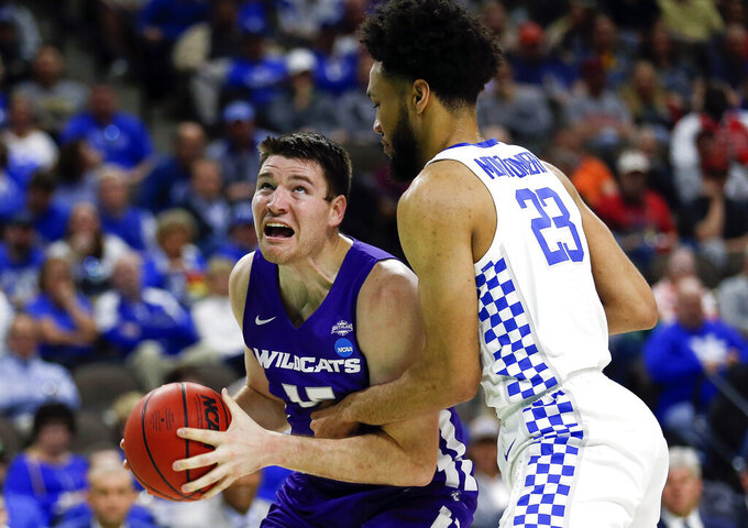 Abilene Christian's Hayden Farquhar, left, looks for a shot as he is defended by Kentucky's EJ Montgomery (23) during the first half of a first-round game in the NCAA men's college basketball tournament in Jacksonville, Fla., Thursday, March 21, 2019. (AP Photo/Stephen B. Morton)