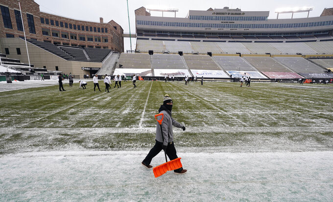 A field worker carries his shovel to help in cleaning the field in sub-freezing temperatures and light snow before the first half of an NCAA college football game as Colorado hosts Utah Saturday, Dec. 12, 2020, in Boulder, Colo. (AP Photo/David Zalubowski)