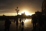 People enjoy a golden sunset in Venice Sunday, , Italy, Sunday, Nov. 17, 2019, just hours after an exceptional 1.5 meter tide receded from nearby St. Mark's Square. It was the third flood topping 1.5 meters this week, following Tuesday's 1.87-meter flood which was the worst in 53 years. In background is Chiesa della Salute church, in Venice, Italy. (AP Photo/Luca Bruno)