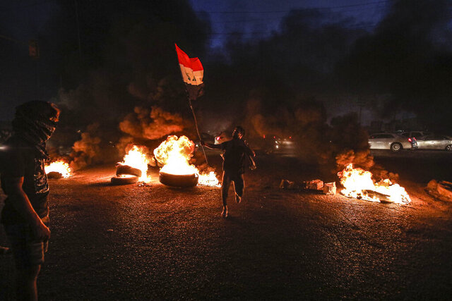 Protesters burn tires during a demonstration demanding better public services and jobs in Basra, southeast of Baghdad, Iraq, Monday, July 27, 2020. (AP Photo/Nabil al-Jurani)