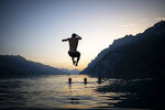 Young people enjoy the evening on lake Walensee, on Tuesday, June 25, 2019, in Walenstadt, Switzerland. The country was hit by a heatwave with temperatures up to 39 degrees celsius. (Gian Ehrenzeller/Keystone via AP)