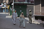 "Kashmiris walk past a paramilitary soldier standing guard during curfew in Srinagar, Indian controlled Kashmir, Tuesday, Aug. 4, 2020. Authorities clamped a curfew in many parts of Indian-controlled Kashmir on Tuesday, a day ahead of the first anniversary of India's controversial decision to revoke the disputed region's semi-autonomy. Shahid Iqbal Choudhary, a civil administrator, said the security lockdown was clamped in the region's main city of Srinagar in view of information about protests planned by anti-India groups to mark Aug. 5 as ""black day."