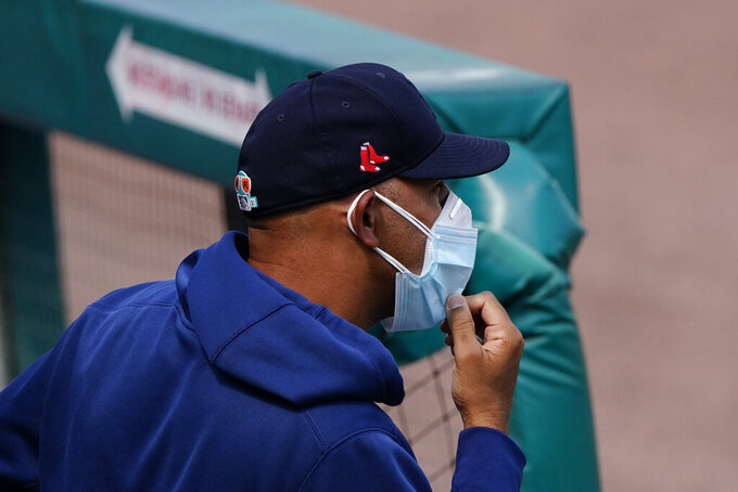 Boston Red Sox manager Alex Cora watches from the dugout during a spring training baseball game against the Atlanta Braves, Wednesday, March 10, 2021, in Fort Myers, Fla. (AP Photo/John Bazemore)