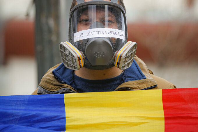 """A man wears a gas mask with the text """"Down the Medical Dictatorship"""" on it, during a protest against the COVID-19 pandemic restrictions in Bucharest, Romania, Saturday, April 3, 2021. Hundreds of anti-restriction protesters took to the streets in several cities across Romania. (AP Photo/Vadim Ghirda)"""