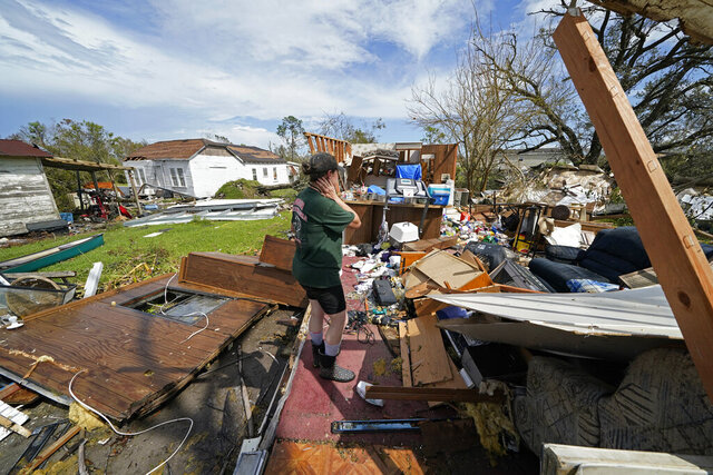 Nicole Beard searches for belongings in the debris of what was the trailer home where she lived in Hackberry, La., in the aftermath of Hurricane Laura, Saturday, Aug. 29, 2020. (AP Photo/Gerald Herbert)