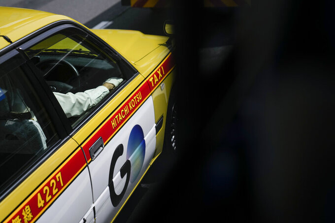 A taxi driver wears a white glove ahead of the 2020 Summer Olympics, Tuesday, July 13, 2021, in Tokyo. (AP Photo/Jae C. Hong)