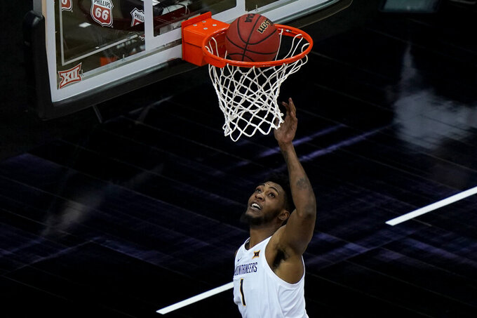 West Virginia's Derek Culver puts up a shot during the first half of an NCAA college basketball game against Oklahoma State in the second round of the Big 12 Conference tournament in Kansas City, Mo., Thursday, March 11, 2021. (AP Photo/Charlie Riedel)