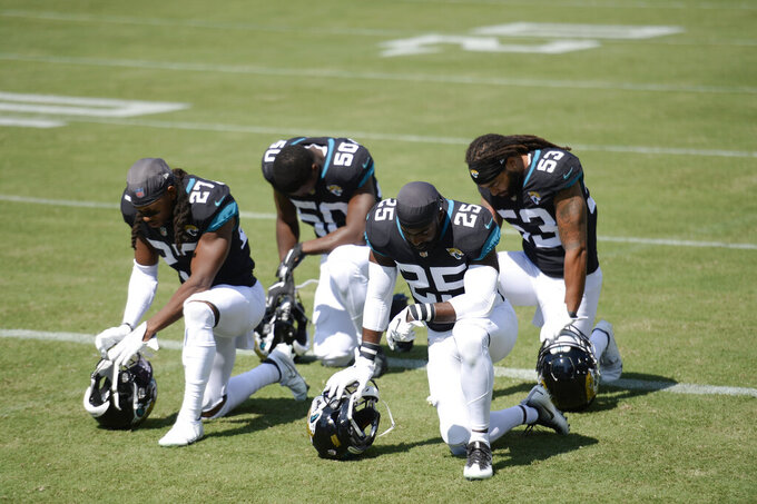 Jacksonville Jaguars players Chris Claybrooks (27), Shaquille Quarterman (50), D.J. Hayden (25) and Dakota Allen (53) kneel before an NFL football game against the Tennessee Titans Sunday, Sept. 20, 2020, in Nashville, Tenn. (AP Photo/Mark Zaleski)