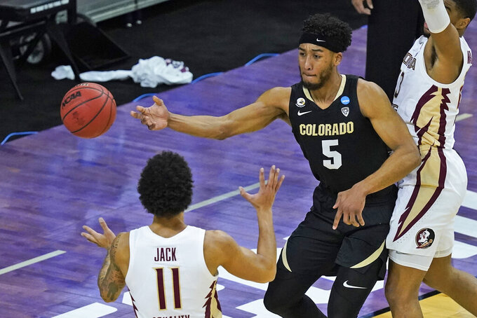Colorado guard D'Shawn Schwartz (5) passes the ball around Florida State guard Nathanael Jack (11) during the first half of a second-round game in the NCAA college basketball tournament at Farmers Coliseum in Indianapolis, Monday, March 22, 2021. (AP Photo/Charles Rex Arbogast)