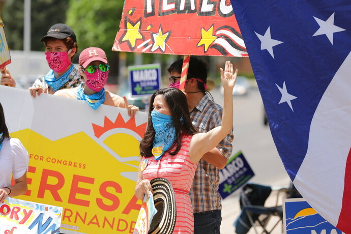 Democratic congressional candidate Teresa Leger Fernandez, in the blue mask, cheers on supporters at a polling station Tuesday, June 2, 2020, in Santa Fe, N.M. Fernandez was flanked by her three sons, left to right, Alisandro, Dario and Abelino. The sign she holds,