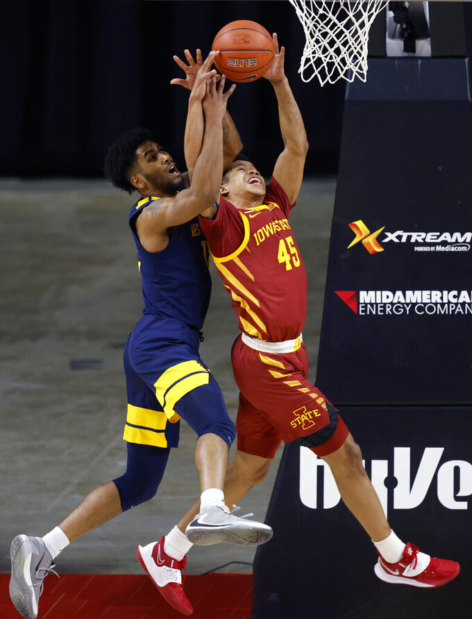 West Virginia guard Taz Sherman, left, battles for a rebound with Iowa State guard Rasir Bolton during the first half of an NCAA college basketball game, Tuesday, Feb. 2, 2021, in Ames, Iowa. (AP Photo/Matthew Putney)