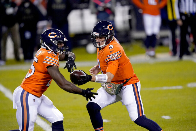 Chicago Bears quarterback Nick Foles (9) fakes a hand off to running back Lamar Miller during the first half of an NFL football game against the Minnesota Vikings Monday, Nov. 16, 2020, in Chicago. (AP Photo/Charles Rex Arbogast)