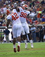 FILE - in this Sept. 22, 2018, file photo, Clemson defensive end Clelin Ferrell (99) and defensive lineman Christian Wilkins (42) celebrate a tackle against Georgia Tech during the first half of an NCAA college football game in Atlanta. Despite adding receiver Devin Funchess and linebacker Justin Houston in free agency, Indianapolis Colts general manager Chris Ballard could be seeking another young receiver to help quarterback Andrew Luck and another pass-rusher to pressure opponents. Some of the names being bandied about include Mississippi receiver A.J. Brown and three Clemson defensive linemen: Wilkins, Ferrell and Dexter Lawrence. (AP Photo/Jon Barash, File)