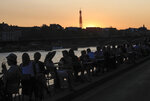 People enjoy drinks along the Seine river bank duringsun set in Paris, Thursday, Sept. 17, 2020. Health Minister Olivier Veran announced 20 more testing centers nationwide as he told a press conference that the virus is