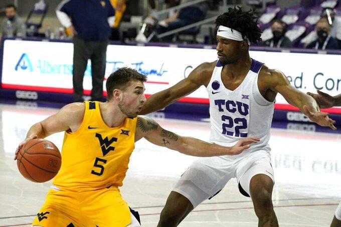 West Virginia guard Jordan McCabe (5) works against TCU guard RJ Nembhard (22) in the first half of an NCAA college basketball game in Fort Worth, Texas, Tuesday, Feb. 23, 2021. (AP Photo/Tony Gutierrez)
