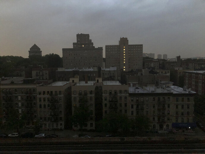 Buildings in Harlem sit dark during a power outage early, Friday, Aug. 7, 2020, in New York. A power outage cast darkness across dozens of blocks in New York City as many people in the city were still without electricity in the aftermath of Tropical Storm Isaias. Con Edison said that a problem with its transmission system