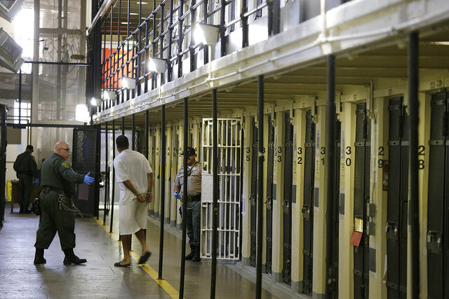 FILE - In this Aug. 16, 2016 file photo, a condemned inmate is led out of his east block cell on death row at San Quentin State Prison in San Quentin, Calif. The California Labor and Workforce Development Agency confirmed Tuesday, Dec. 1, 2020, that California has sent about $400 million in unemployment benefits to state prison inmates. In all records show 31,000 inmates have applied for benefits and about 20,800 were paid $400 million. A group of local and federal prosecutors said 133 inmates on death row were named in claims. (AP Photo/Eric Risberg, File)
