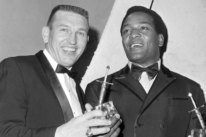 FILE - In this Feb. 14, 1968, file photo, Johnny Unitas, left, of the Baltimore Colts poses with Jim Brown during an awards ceremony in Hollywood, Calif. Unitas emerged as a star in the late 1950s when he led Baltimore to the title in 1958 against the Giants. That success carried over into the next decade when he was the signature quarterback in the league. Cleveland running back Jim Brown only played until 1965 but his impact in the first six years of the '60s was enough to make him perhaps the most dominant player in the NFL during that period.  (AP Photo/Harold P. Matosian, File)